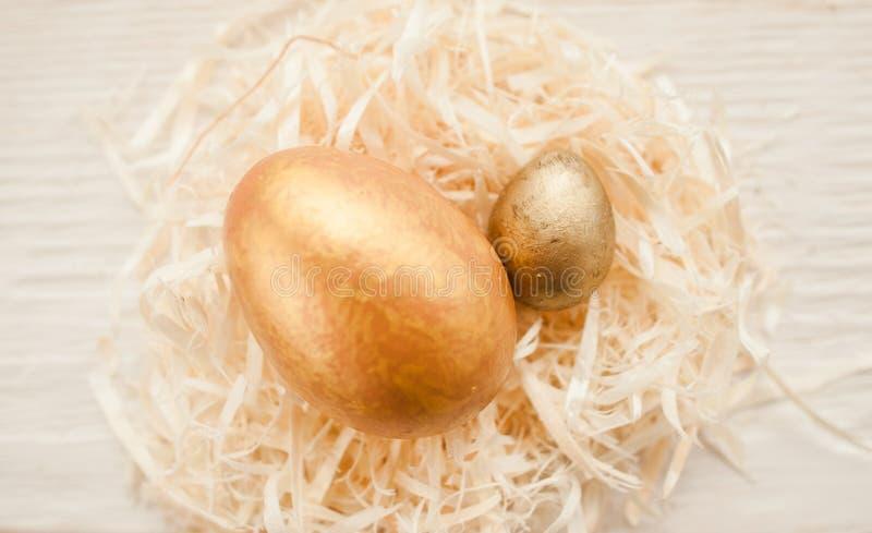 Deux oeufs de pâques d'or dans la décoration blanche de nid photos stock
