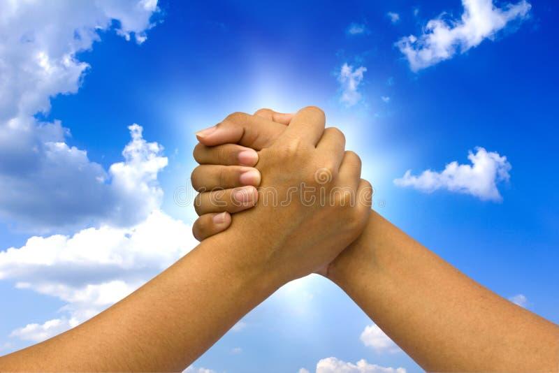 Deux ont accouplé des mains, sur le ciel. images stock