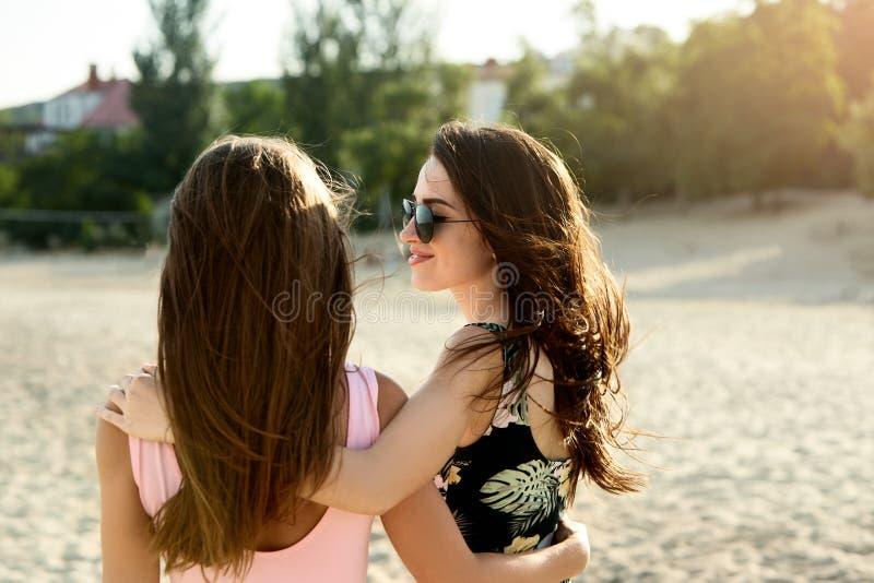 Deux ont bronzé des amis prenant un bain de soleil sur la plage et ayant l'amusement Les filles utilisant les maillots de bain et image libre de droits