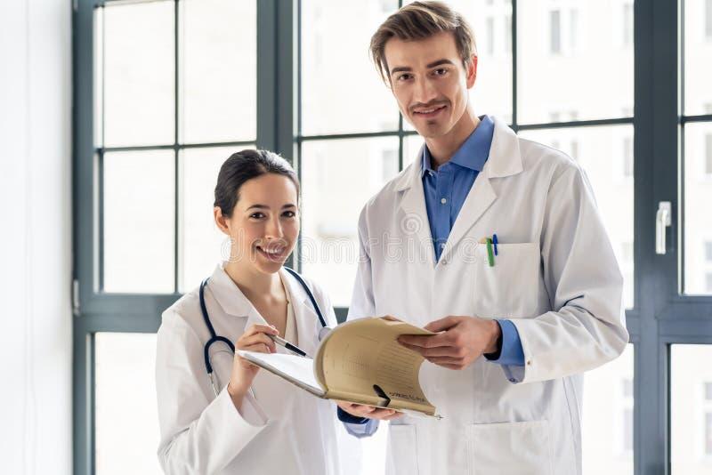 Deux ont consacré des médecins souriant tout en tenant un dossier avec les disques médicaux photos stock