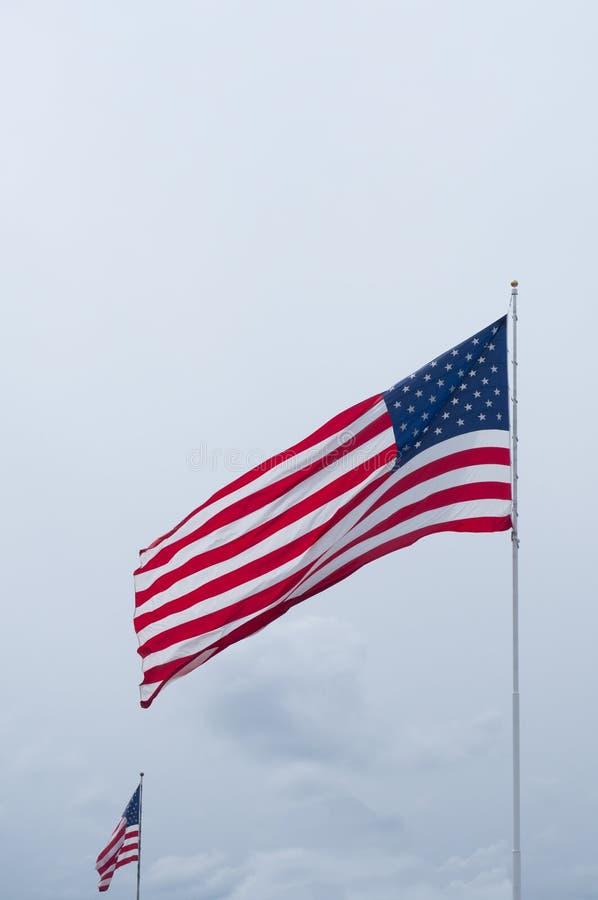 Deux ont déferlé les drapeaux américains contre un ciel nuageux photographie stock libre de droits