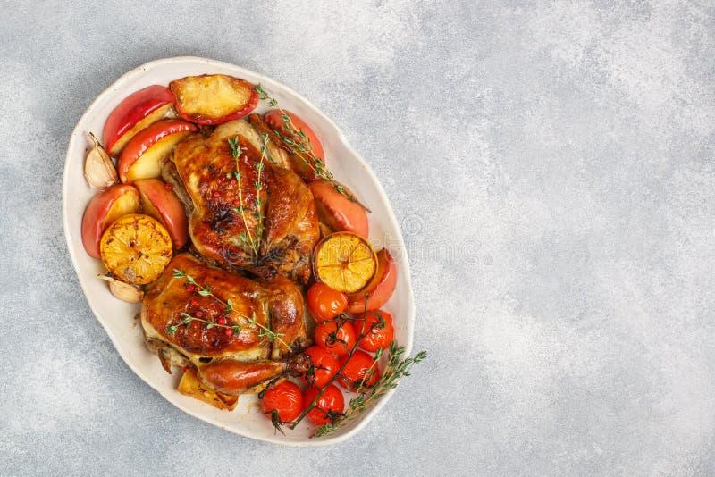 Deux ont fait de jeunes poulets cuire au four entiers avec les pommes, le citron, l'ail, le thym, les tomates et les épices images libres de droits
