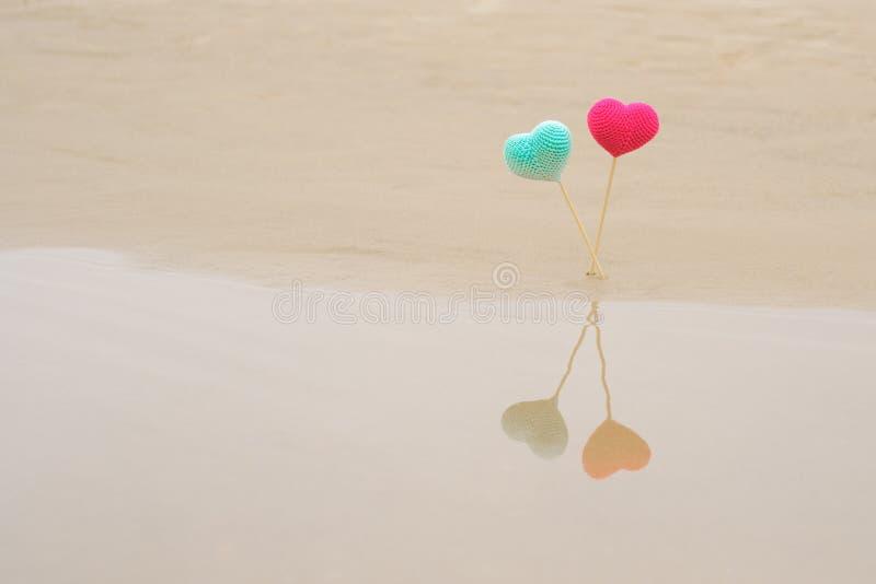 Deux ont fait du crochet les coeurs lumineux et colorés sur les bâtons en bois sur la plage, reflétée dans l'eau Coeurs rouge-ros photo libre de droits
