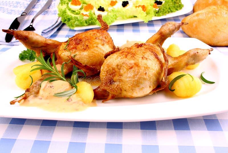Deux ont fait frire des cailles avec de la salade de sauce au jus, de gnocchi, de romarin et de caviar images stock