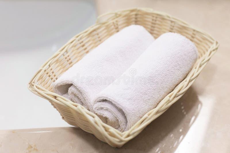 Deux ont roulé les serviettes de main blanches dans le panier rectangulaire léger sur photographie stock