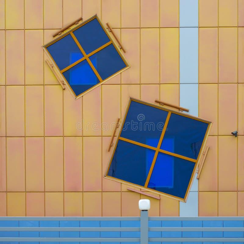 Deux ont tourné des fenêtres sur la façade du bâtiment dans la ville images stock