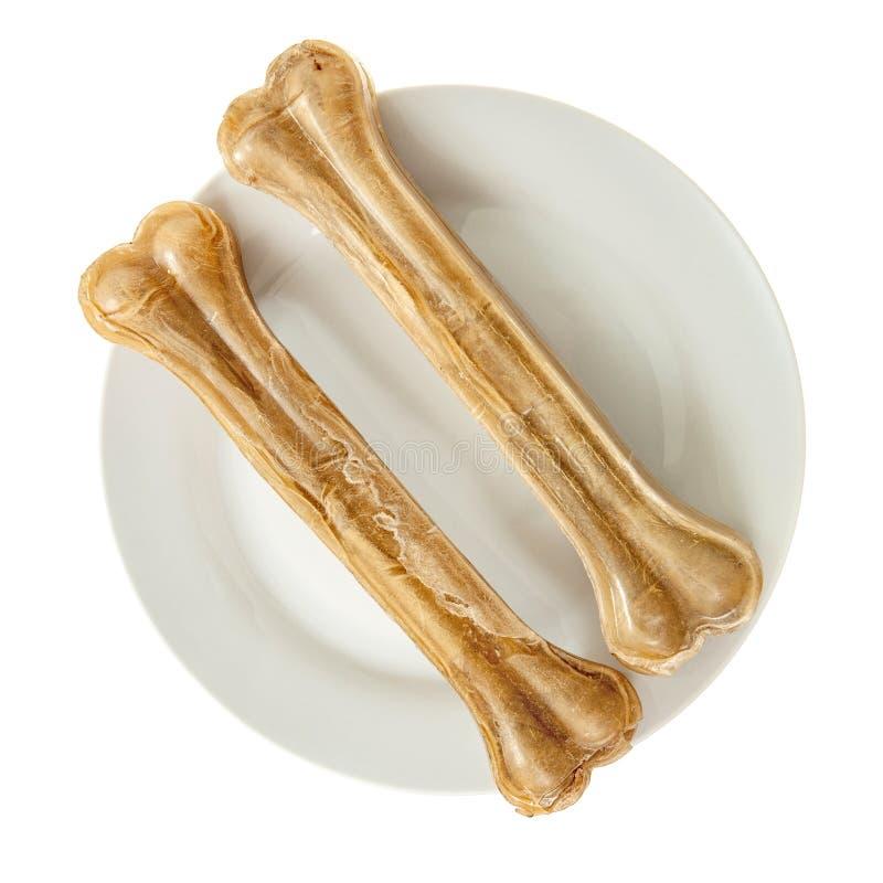 Deux os de chien de mastication du plat d'isolement photographie stock