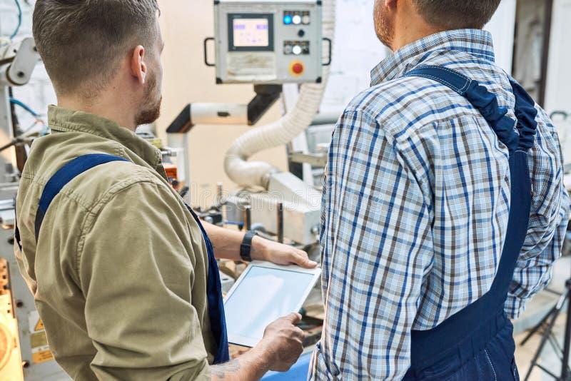 Deux ouvriers actionnant des unités de machine images libres de droits