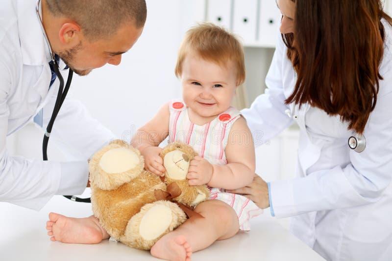 Deux pédiatres prennent soin de bébé dans l'hôpital La petite fille examine par le docteur avec le stéthoscope santé photo libre de droits