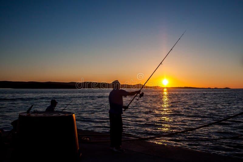 Deux pêcheurs au coucher du soleil en Croatie photographie stock libre de droits