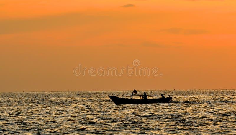 Deux pêcheurs prennent un petit bateau de pêche à la mer au coucher du soleil photo stock