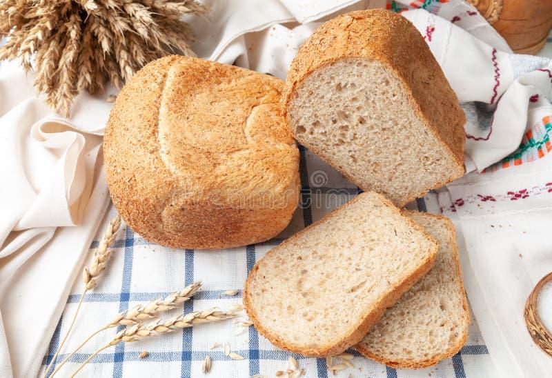 Deux pains de son Sur une nappe blanche rayée bleue Sur la nappe se trouvent deux ? tranchées ? morceaux de pain, des oreilles de images libres de droits