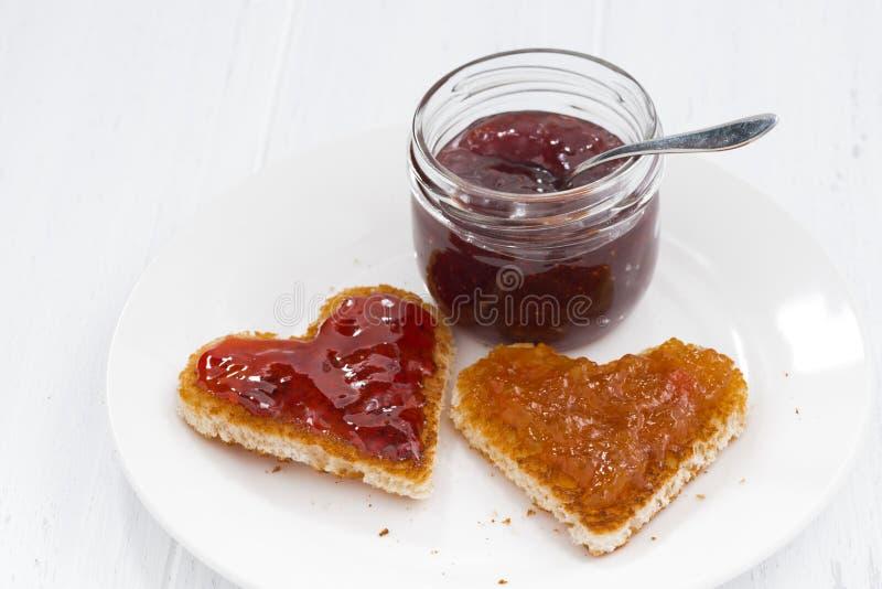 Deux pains grillés dans la forme de coeur avec le fruit bloque du plat images stock