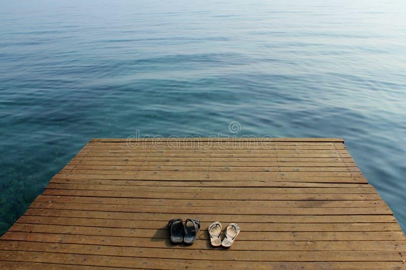 Deux paires de bascules sur la plate-forme en bois près du bord de la mer photo libre de droits