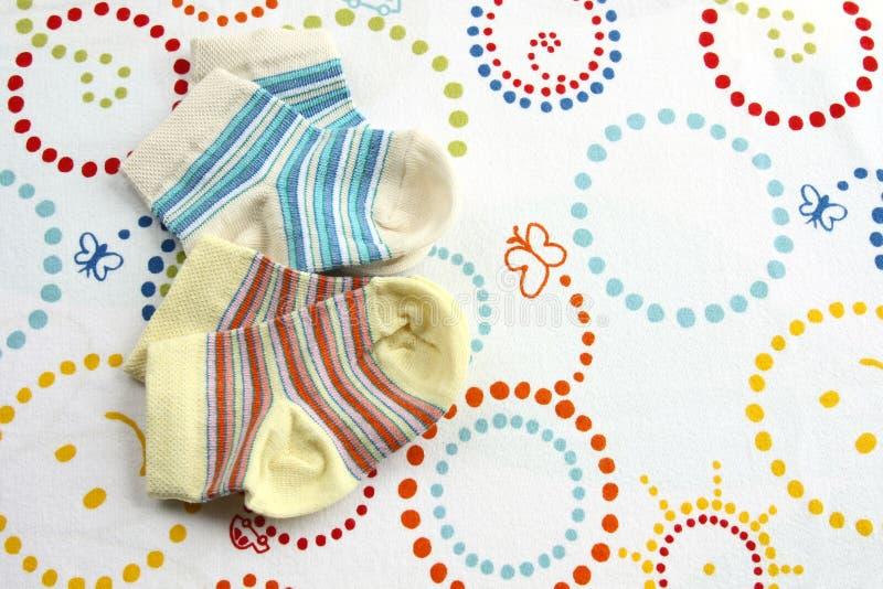 Deux paires de chaussettes de bébé : rayé bleu et jaune photos libres de droits