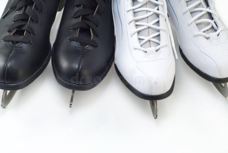 Deux paires de figure patins noire et blanche se ferment-u photographie stock libre de droits