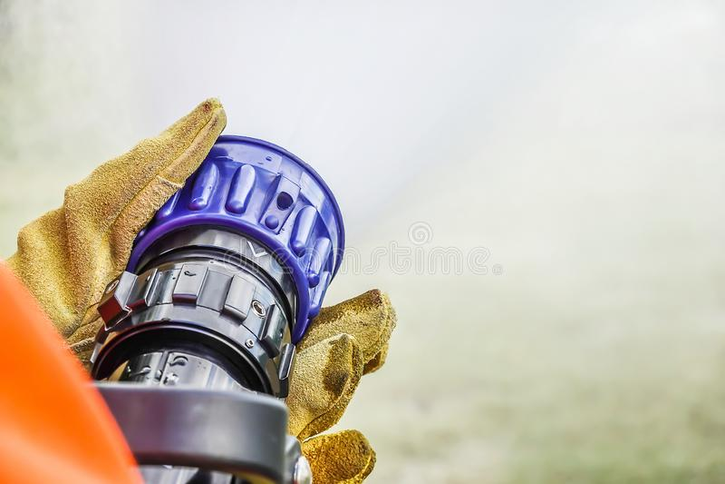 Deux paires de mains tenant la poignée sur la fin de l'des pompiers arrosent l'eau de pulvérisation de tuyau pendant la pratique photos libres de droits
