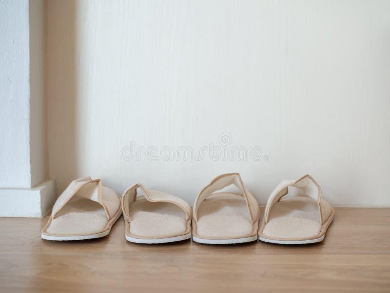 Deux paires de pantoufles molles blanches sur le plancher en bois sur le fond blanc de mur image libre de droits