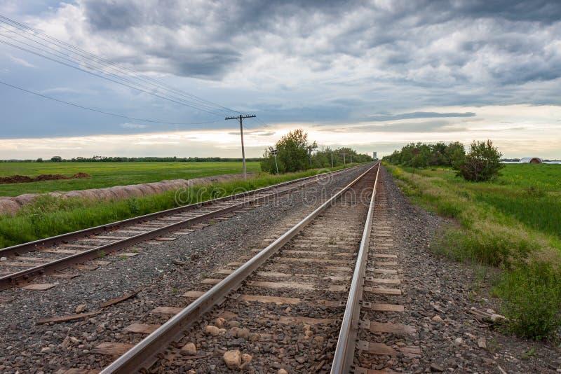 Deux paires de voies menant au ciel nuageux image stock