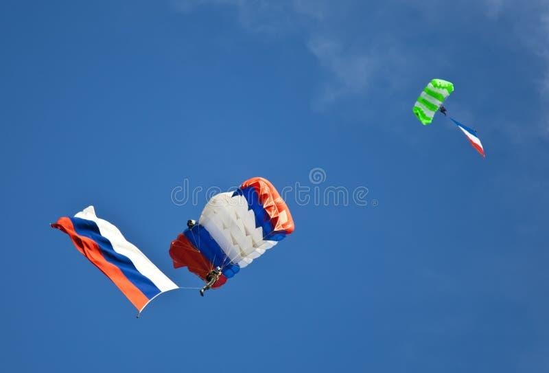 Deux parachutistes glissant avec les drapeaux russes sur le fond de ciel bleu image libre de droits