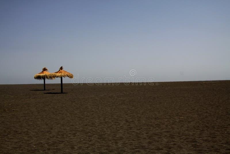 Deux parapluies tubulaires différant du sable noir de lave sur la plage isolée - Cobquecura Piedra De La Loberia, Chili photographie stock