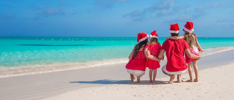 Deux parents et enfants en Santa Hat sur la plage blanche photo libre de droits