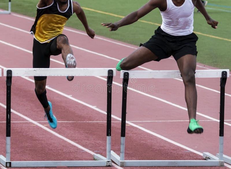 Deux participants à une course d'obstacles vainquant la finale straigtaway photographie stock