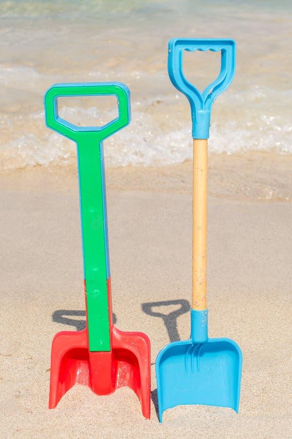 Deux pelles coincées sur la plage dans le sable images libres de droits