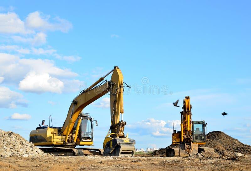 Deux pelles jaunes sur un chantier de construction Excavateur avec godet de broyeur pour écraser le béton image libre de droits