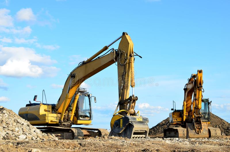 Deux pelles jaunes sur un chantier de construction Excavateur avec godet de broyeur pour écraser le béton image stock