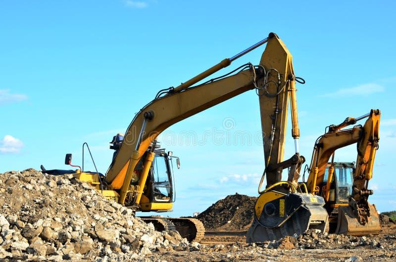Deux pelles jaunes sur un chantier de construction Excavateur avec godet de broyeur pour écraser le béton photographie stock