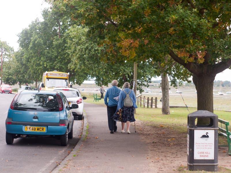Deux personnes âgées marchant par derrière vers le bas le trottoir dans le pays photographie stock libre de droits