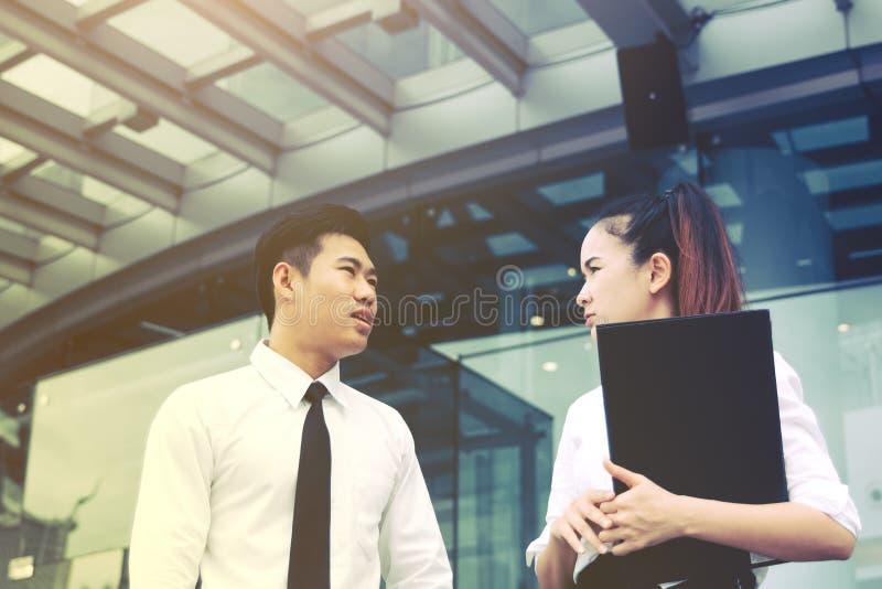 Deux personnes asiatiques d'affaires se tenant devant l'immeuble de bureaux a photos libres de droits