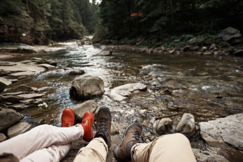 Deux personnes détendant par la rivière et les chaussures confortables de port images stock