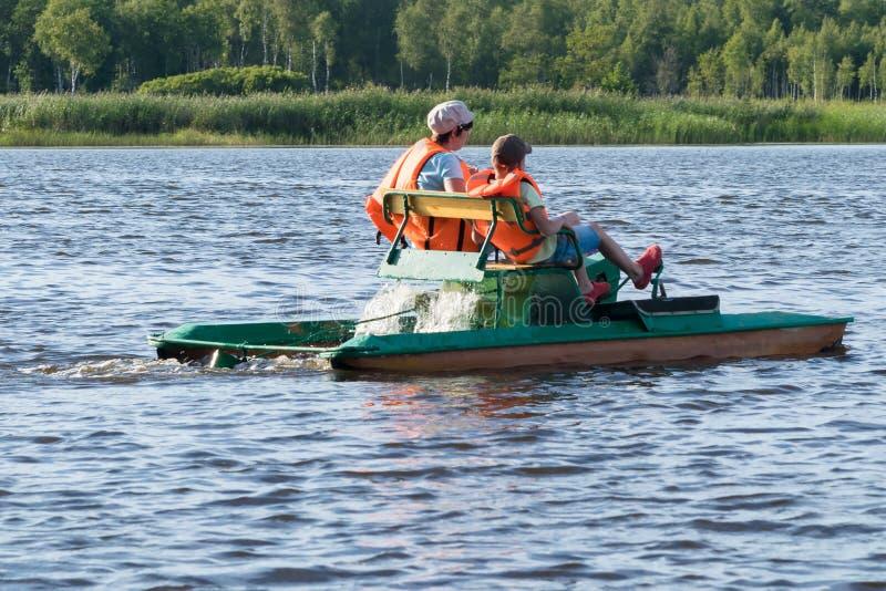 Deux personnes dans des gilets de sauvetage montent sur un bateau de fer sur la rivière, vue arrière photos libres de droits