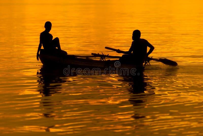 Deux personnes dans un petit bateau au coucher du soleil orange et d'or photo libre de droits