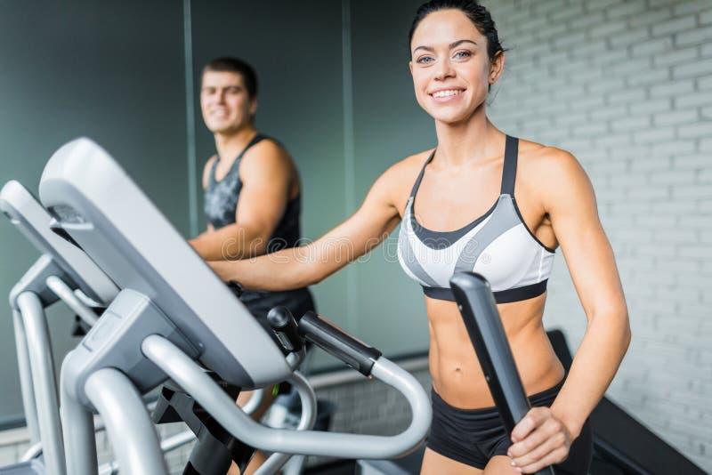 Deux personnes de forme physique à l'aide des machines dans le gymnase photo stock