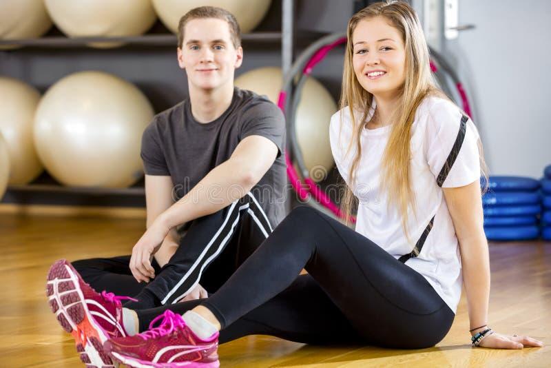 Deux personnes de sourire ayant une coupure au gymnase de forme physique photos libres de droits