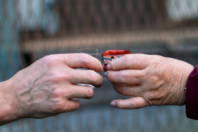 Deux personnes différentes grillant à la santé et à bon harvesty dans leurs lifes Les mains de la femme et de l'homme tiennen photo libre de droits