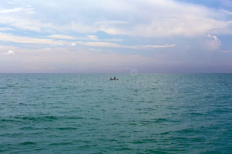 Deux personnes en mer dans un canot en caoutchouc Mer tropicale de bleu de turquoise images libres de droits