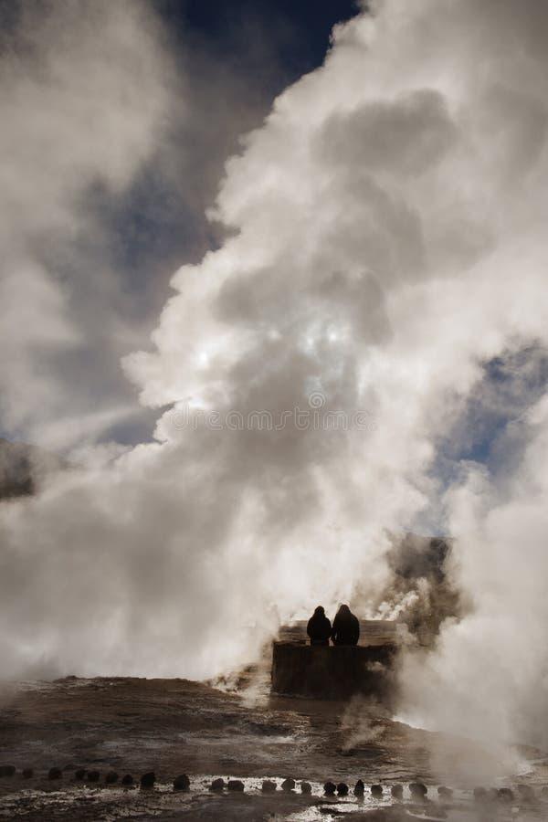 Deux personnes enfoncées au geyser de Tatio au lever de soleil photos libres de droits