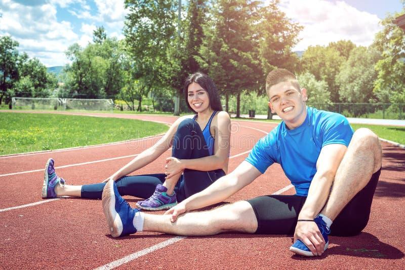 Deux personnes faisant étirant l'exercice extérieur photos stock