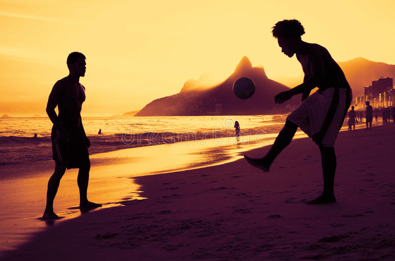 Deux personnes jouant le football à la plage à Rio au coucher du soleil photographie stock libre de droits