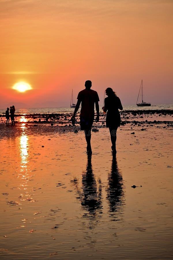 Deux personnes marchant pendant le coucher du soleil photographie stock