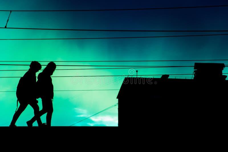 Deux personnes marchant sur le fond de ciel et de fils avec des silhouettes, maison au-dessus de elles photos libres de droits