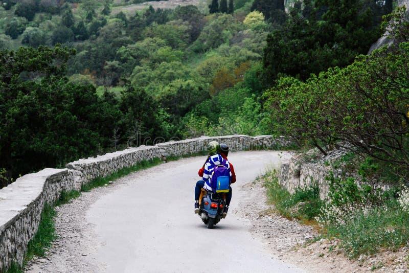 Deux personnes montant une route de montagne sur un scooter de cru Conceptuellement pour des voyageurs et des amants des scooters photo stock
