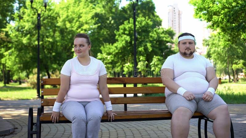 Deux personnes obèses mignonnes s'asseyant modestement sur le banc, lancent aussi pour devenir au courant photos stock