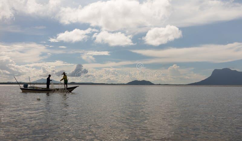 Deux personnes pêchant avec le filet d'un bateau dans Sarawak, Bornéo photographie stock libre de droits