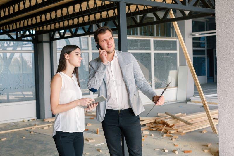 Deux personnes se tiennent près du chantier de construction, le type parlent au téléphone images libres de droits