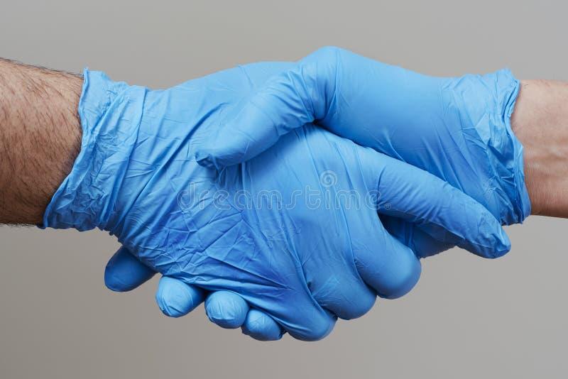 Deux personnes serrant la main avec des gants chirurgicaux image stock